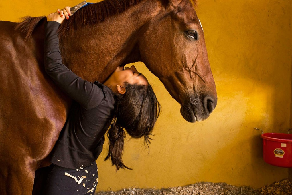 photo of a girl hugging a horse
